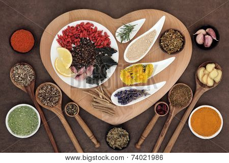 Superfood immune boosting selection in white porcelain dishes and wooden bowls over heart shaped board and lokta paper background.
