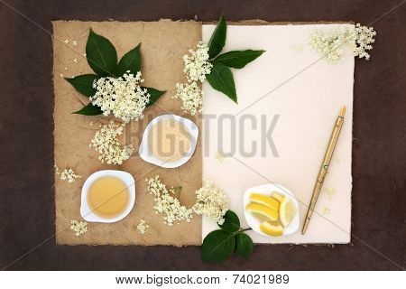 Elderflower champagne ingredients with old pen over natural hemp notebook and lokta paper background.