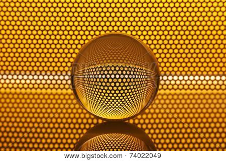 Abstract background with glass ball. Metal mesh refracted in glass sphere.