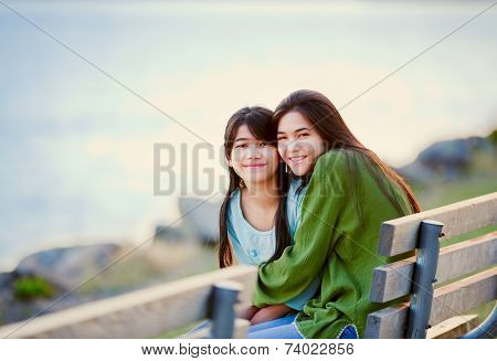 Two Sisters, Friends Sitting By Lake Together