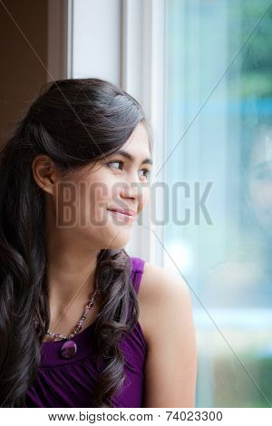 Beautiful Biracial Young Woman Smiling By Window