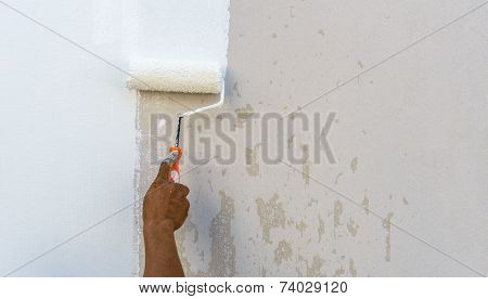 Worker Spends Roller Paint On The Wall