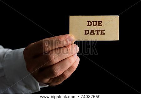 Man Holding A Wooden Sign Saying Due Date