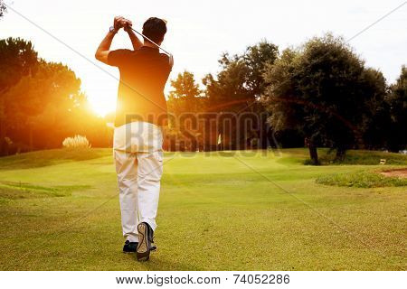 Good strike, golfer swinging his driver and looking away