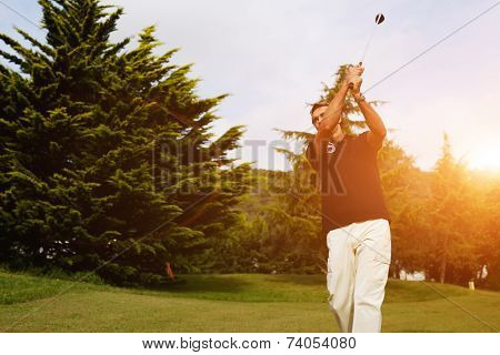 Strong golf shot of player standing on golf course