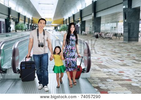 Family Walking In The Airport Hall