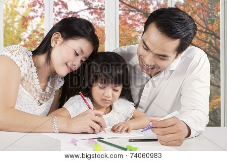Two Parents Assist Their Child Studying