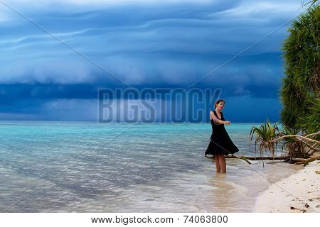 Beautiful Young Woman Dancing On The Beach With A Tropical Storm Coming