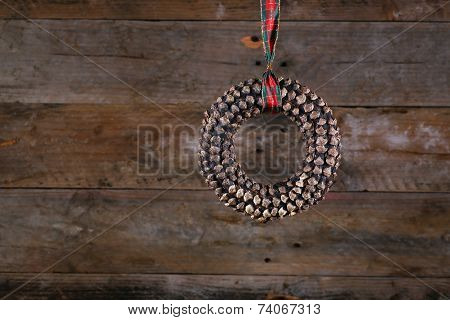 Round Shape Pine Cone Christmas Wreath And Ribbon On Old Rustic Background