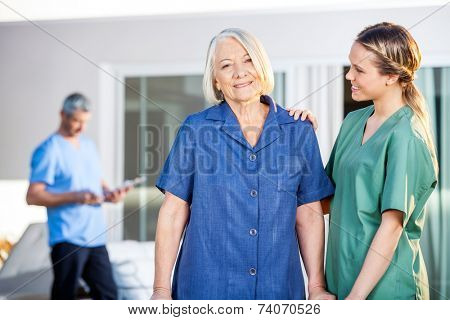 Portrait of smiling senior woman being assisted by female caretaker in nursing home