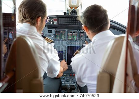 Rear view of pilot and copilot operating controls of corporate jet