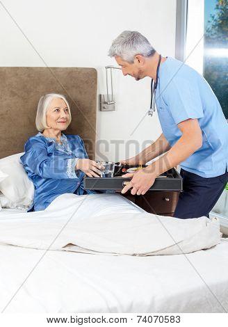 Male caretaker serving breakfast to senior woman on bed in nursing home