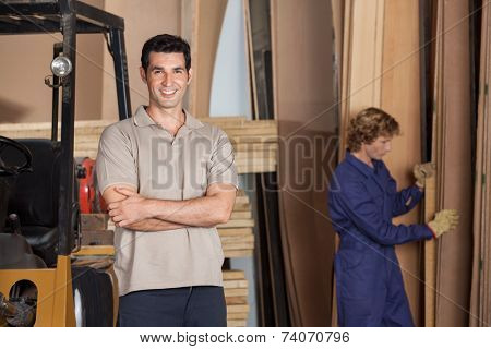 Portrait of confident carpenter with arms crossed standing in workshop