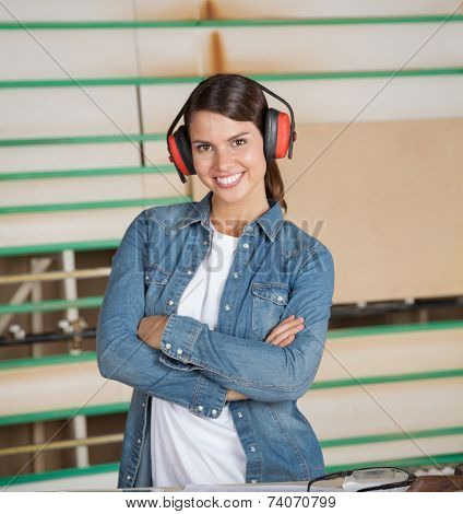 Portrait of confident female carpenter wearing ear protectors in workshop