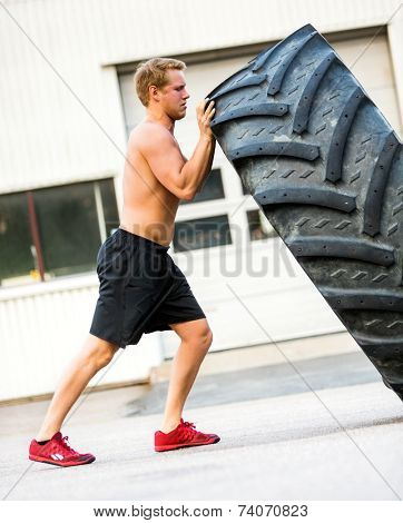 Full length side view of male athlete doing tire-flip exercise outside gym