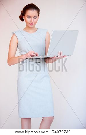 Standing Young Pretty Lady in Very Light Blue Sleeveless Dress Using Apple Laptop. Isolated on Off- White Background.