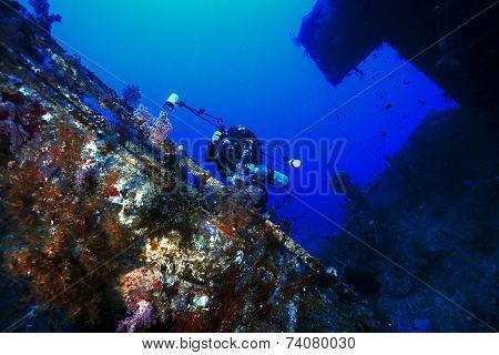 deep scuba diver exploring and photographing a deep wreck