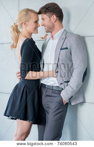 Sweet Middle Age Couple Smiling Each Other Isolated on Light Gray Building Wall Background