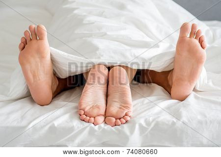 Close up Sweet Couple Feet Soles on Bed with White Cover