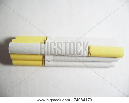 Five Cigarettes Laying Along On The White Background
