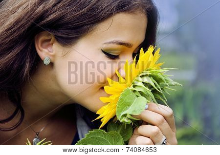Nice Plump Girl Smelling A Sunflower