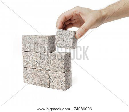 Man making a square shape of blocks made of granite rock.