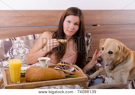 Beautiful Young Woman Eating Breakfast In Bed In The Morning With Dog