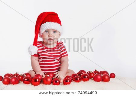 Toddler playing with red balls for the Christmas tree.