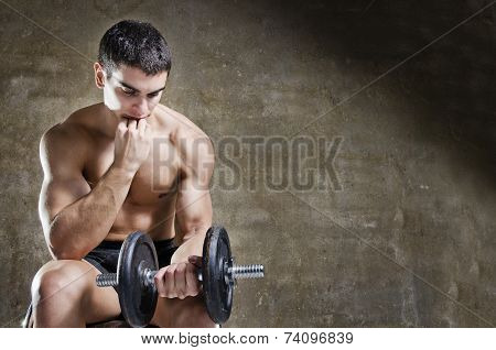 Thoughtful And Relaxed Man Training With Dumbbell
