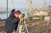 picture of cartographer  - Engineer at the construction site makes measurements with leveling - JPG