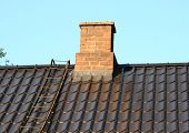 picture of chimney  - Brick chimney on black roof with metal ladder - JPG