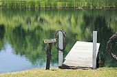 "pic of dock a pond  - ""Beware of Attack Alligator"" sign on the shores of a sunny pond. - JPG"