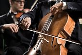 pic of orchestra  - Cello professional player with symphony orchestra performing in concert on background - JPG