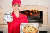 foto of take out pizza  - Beautiful delivery woman with delicious pizza in pizza box and clock - JPG