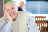 picture of day care center  - Portrait of smiling senior man sitting at nursing home with grandson in background - JPG