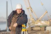 foto of cartographer  - Engineer at the construction site makes measurements with leveling - JPG