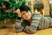 stock photo of cozy hearth  - Woman lying on wooden floor near fireplace with Christmas fir - JPG