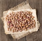 pic of pinto bean  - Pinto beans on a paper and burlap on a wooden table - JPG