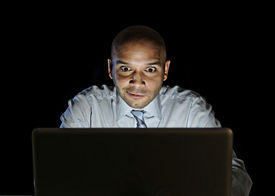 picture of addicted  - young attractive businessman alone at night sitting at computer laptop watching porn or online gambling isolated on black background on internet chat addiction concept - JPG