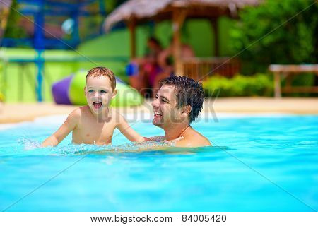 Father And Son Having Fun In Pool, Summer Vacation
