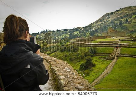 Unidentified tourist taking photos in Ingapirca important Inca ruins in Ecuador