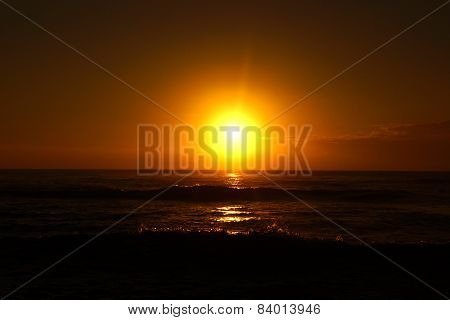 Sunrise Over The Ocean With Waves Crashing Along Shore