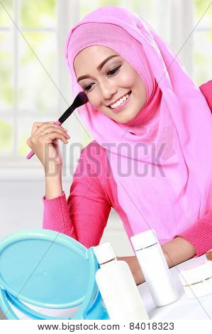 Young Muslim Woman Looking At The Mirror Doing Makeup