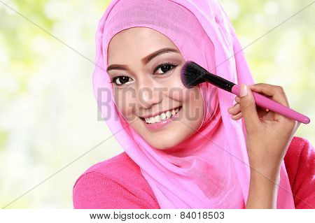 Young Muslim Woman Applying Blush On