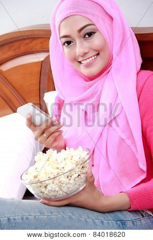 Young Woman Wearing Hijab Holding A Mobilephone And A Bowl Of Popcorn On Bed