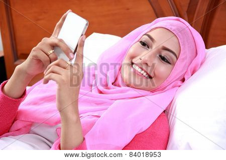 Young Muslim Woman Lying On Bed While Playing Mobilephone