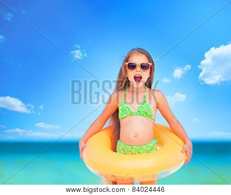 Child With Sunglasses And Inflatable Ring At The Beach