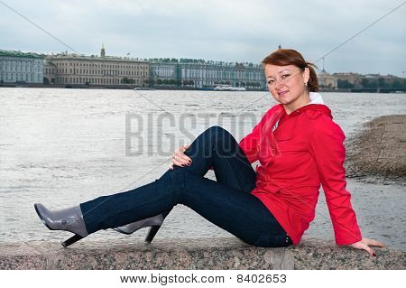 Young Woman Sitting On Embankment