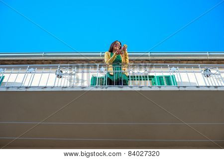 Woman with phone on the balcony