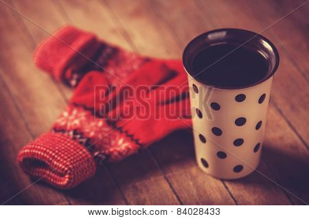 Cup Of Coffee And Mittens On Wooden Table.